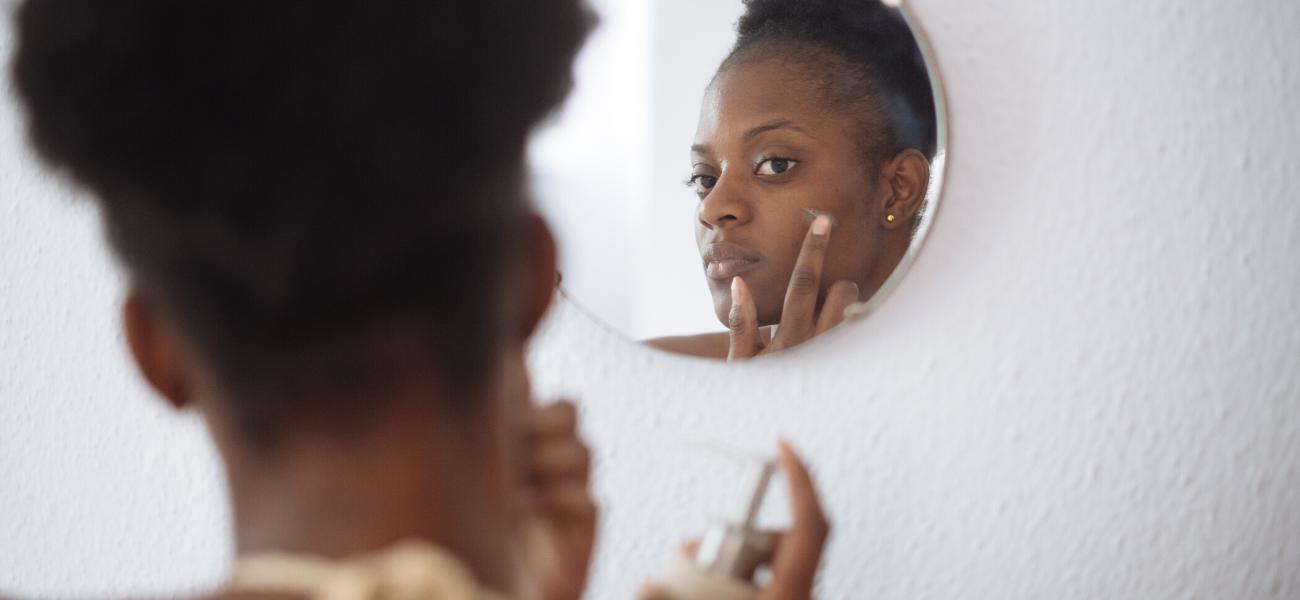mujer aplicando vitamina E en la piel