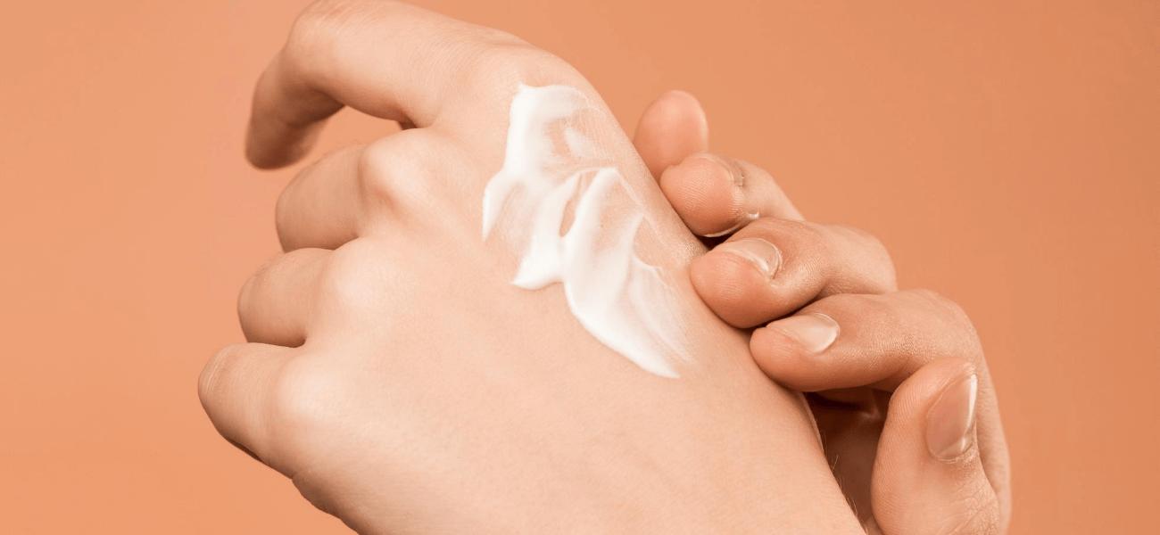 mujer aplicando crema en las manos